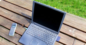 An image of a laptop and wireless phone on a picnic table