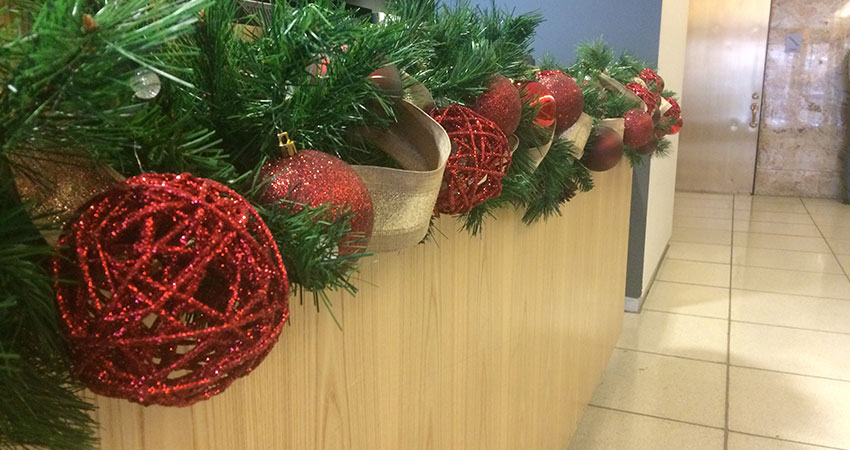 An image of garland and ornaments placed along a reception desk countertop